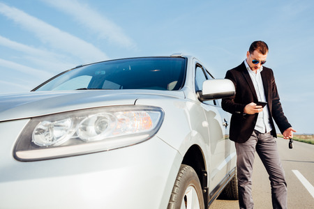 establishes: Man using a mobile phone next to the car Stock Photo