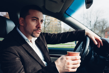 car driving: Man drinking coffee while driving the car Stock Photo