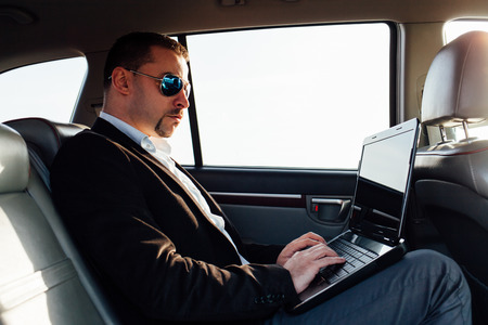 back seat: Young businessman using laptop in back seat of car Stock Photo