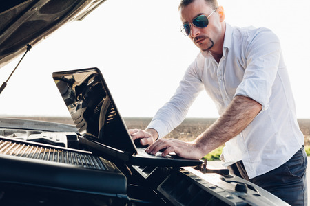 malfunction: Modern man using a laptop to detect malfunction in the car on the road
