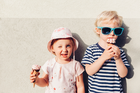 Adorable girl and boy eating ice cream