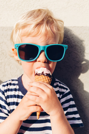 Closeup of little boy with sunglasses eating ice cream at sunset