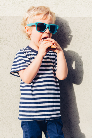 Cute kid boy with sunglasses eating ice cream at sunset Stock Photo