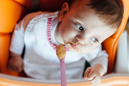 eat smeared baby: Mother feeding baby with a spoon Stock Photo