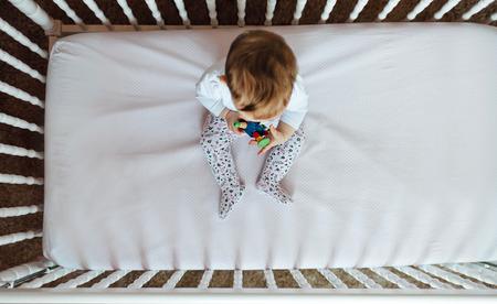 mattress: Cute little funny baby in crib