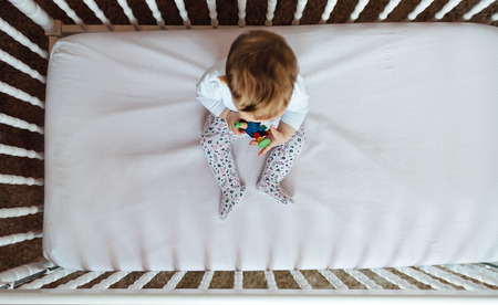 Cute little funny baby in crib