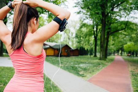 binding: Beautiful young woman binding long hair before running in the park