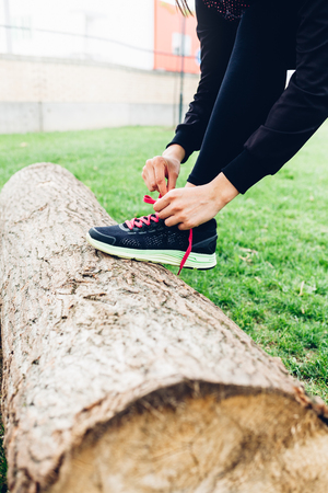 felled: Closeup of woman tying shoelaces on a felled tree
