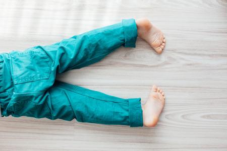 pantalones abajo: Detalle de la joven niño descalzo con pantalones de color turquesa que se establecen en el suelo Foto de archivo