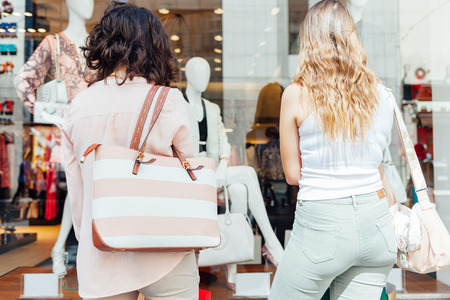showcase: Elegant young women looking at boutique showcase Stock Photo
