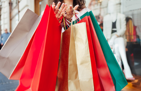 crowded space: Closeup of woman holding shopping bags after shopping Stock Photo