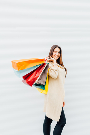 Happy girl holding shopping bags with copy space