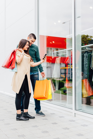 Couple using a mobile phone before entering the store Stock Photo