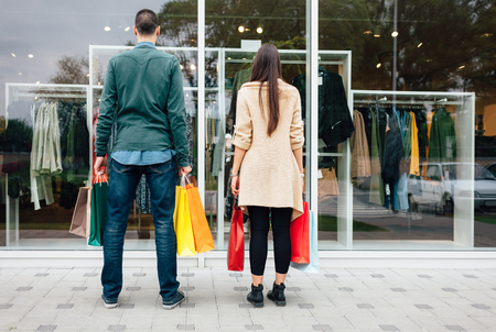 Man and woman with shopping bags looking at store window