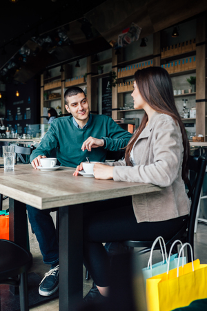 purchase: Couple with shopping bags drink coffee after purchase Stock Photo