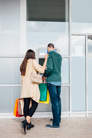 automat: Couple withdrawing money from ATM machine in shopping center with copy space