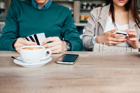 pays: Man pays a coffee with payment card. Copy space on wooden table. Stock Photo
