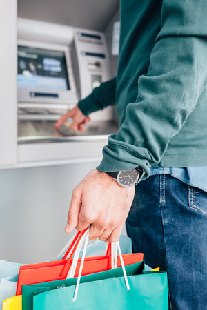 automat: Closeup of man holding colorful shopping bags and entering PIN code on ATM machine