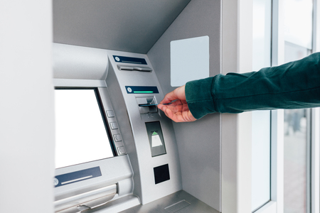 Closeup of man inserting credit card in ATM machine Standard-Bild