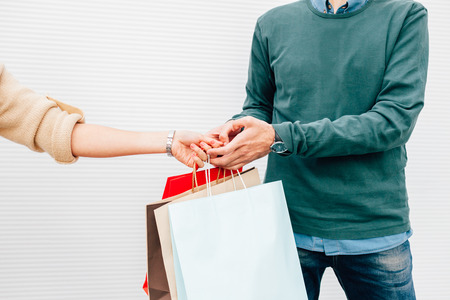 gift bags: Closeup of man giving his wife gift in shopping bags Stock Photo