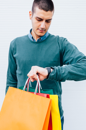 Shopping is finished. Man with shopping bags looking at his watch. Shopping is finished.