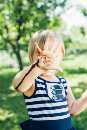 smeared: Little smeared girl looking at leaked hand with ice cream Stock Photo