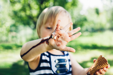 smeared: Girl has leaked ice cream on hand in closeup Stock Photo