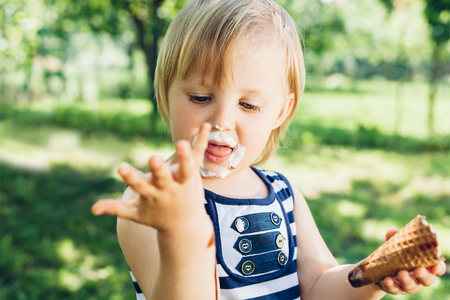 smeared hand: Little smeared girl looking at leaked hand with ice cream Stock Photo