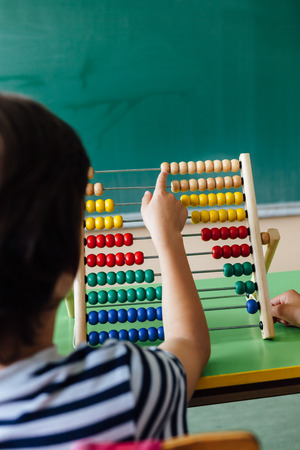 algebra calculator: Child working with abacus in the classroom Stock Photo