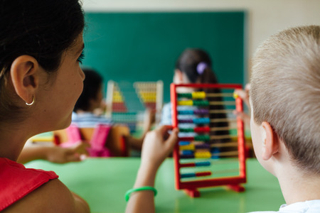 calc: Children working with abacus in the classroom Stock Photo