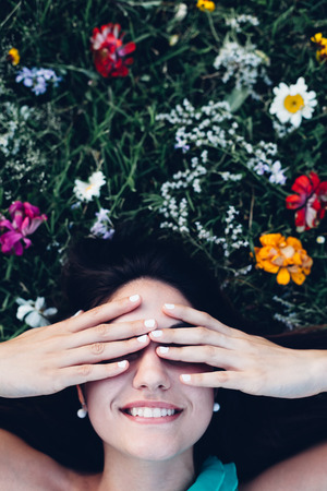hands covering eyes: Portrait of a young woman with hands covering eyes, copy space on grass.