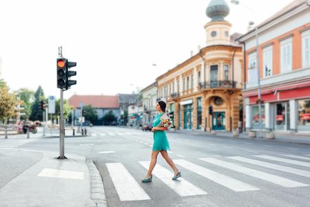 semaforo peatonal: Mujer con estilo que recorre en un paso de peatones en la ciudad con el ramo de flores Foto de archivo