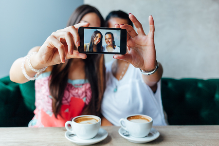 Mother and daughter making selfie in a cafe. Mothers day.