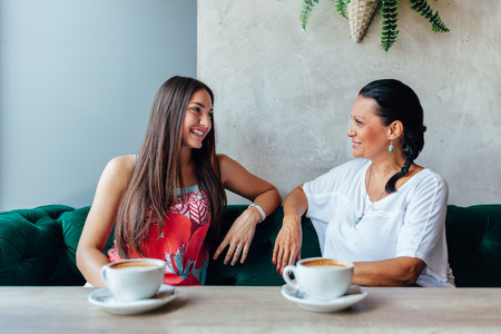 Two happy women talking in cafe. Aged woman and her adult daughter drinking coffee at cafe. Mothers day. Stock Photo