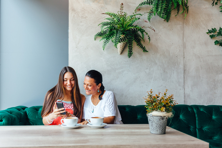 intergenerational: Mother and daughter women using a mobile phone in a cafe