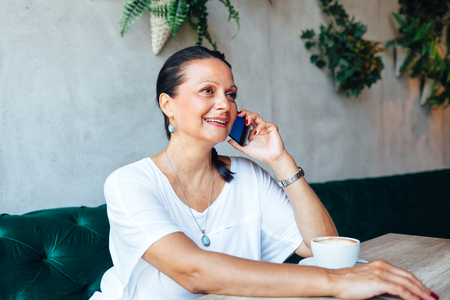 phone calls: Beautiful middle age woman have a phone call in a cafe