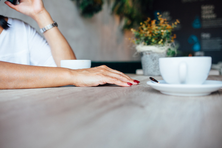 Closeup of woman in a cafe with copy space on the table. Coffee background.
