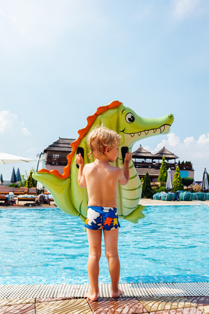 Little boy enters the swimming pool with mattress