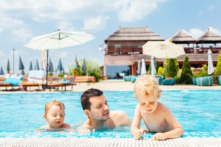 Father with children enters swimming pool