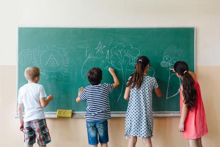 niños escribiendo: Los niños escriben en la pizarra en la escuela