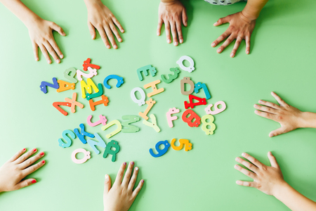 Top view of child hands with wooden toy plate alphabet in classroom