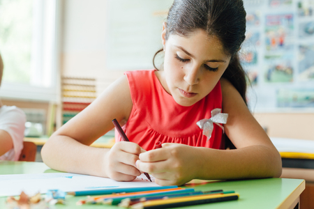 Girl drawing in classroom at school
