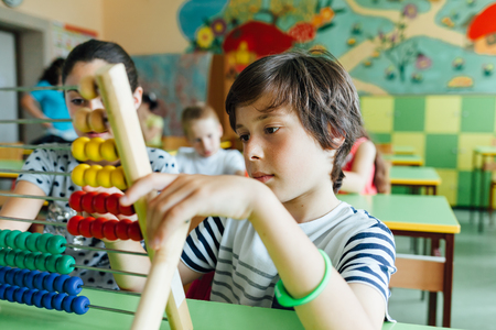 algebra calculator: Closeup of children working with abacus in the classroom