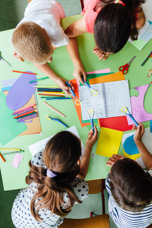 Creative workshop at school. Group of school children learning together in class.