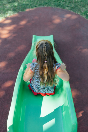 toboggan: Kid playing outdoors on the toboggan. Child at the playground.