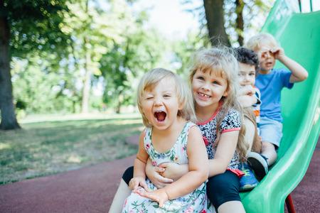 Gelukkig kinderen spelen buiten. Kinderen bij de speelplaats. Stockfoto