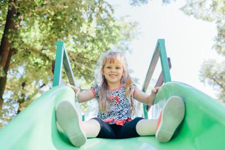 toboggan: Happy girl playing at the playground  outdoors. Kid at the toboggan.