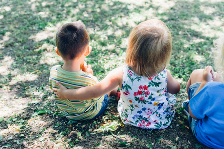 seated: Back view of cute kids seated on grass. Cute girl embracing boy. Stock Photo