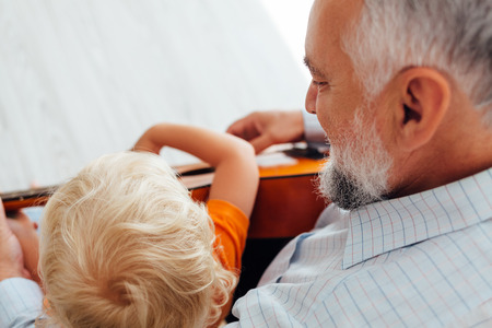 Closeup of happy grandpa learning his grandson to play guitar