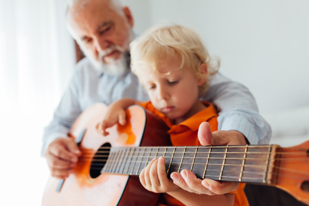 Grandpa learning his grandson to play guitar in closeup